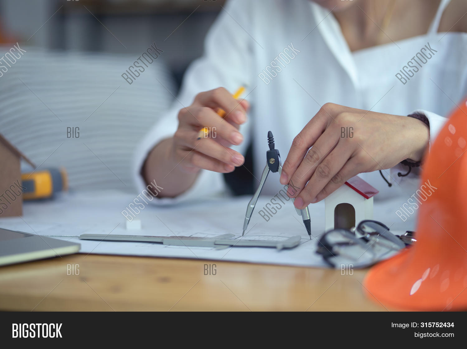 Hands Of Architect Or Engineer Using Compass Working With Blueprint On Desk In Office. Engineering T