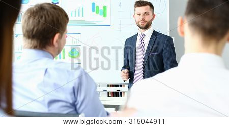 Focus on handsome smiling man. Chief executive officer conducting masterclass for colleagues. Staffs sitting in conference room. Company meeting concept stock photo