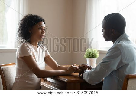 African couple sitting at table having heart-to-heart talk stock photo