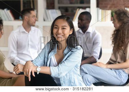 Asian addiction counsellor pose looking at camera during group rehab stock photo