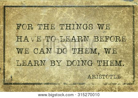 For the things we have to learn before we can do them, we learn by doing them - ancient Greek philosopher Aristotle quote printed on grunge vintage cardboard stock photo