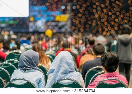 Rear view of Audience in the conference hall or seminar meeting which have Speakers on the stage, business and education about investment concept stock photo