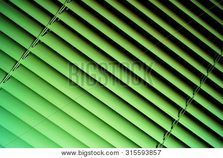 Blinds green background--effective light protection devices from horizontal slats. The slats are stationary or rotated, regulate light and air flow. Blinds are popular in residential, office, industrial premises. stock photo