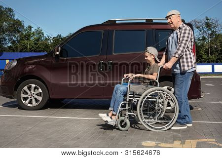 Senior man with boy in wheelchair near van on car parking stock photo