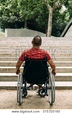 vertical photo of a disabled man on wheelchair stopped in front of stairs who can't climb looking up for help, raising awareness of accessibility issues for people with reduced mobility stock photo