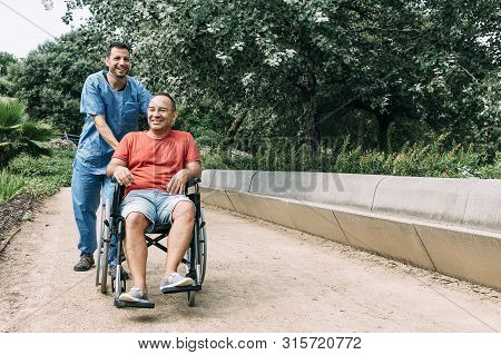 disabled man in wheelchair laughing during a walk with his nurse at park, concept of medical care and rehabilitation of people with disabilities and reduced mobility problems stock photo