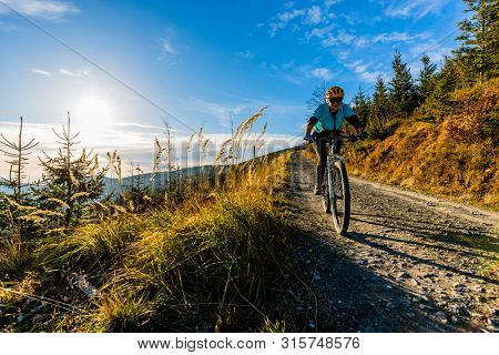 Mountain biking woman riding on bike in autumn mountains forest landscape. Woman cycling MTB flow trail track. Outdoor sport activity. stock photo