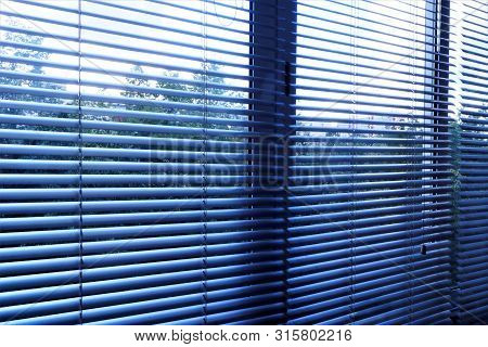 Blinds--effective light-shielding device of the horizontal slats. The slats on the Windows are stationary and swivel, regulate light and air flow. Blinds are popular in residential, office and industrial premises. stock photo