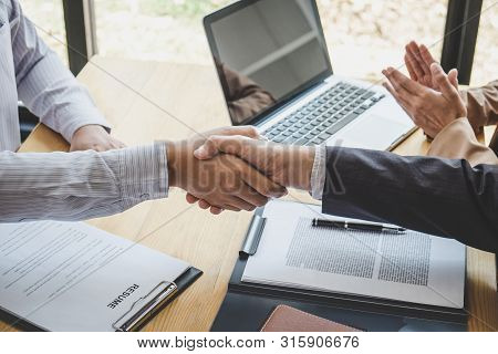 Greeting new colleagues, Handshake while job interviewing, male candidate shaking hands with Interviewer or employer after a job interview, employment and recruitment concept. stock photo