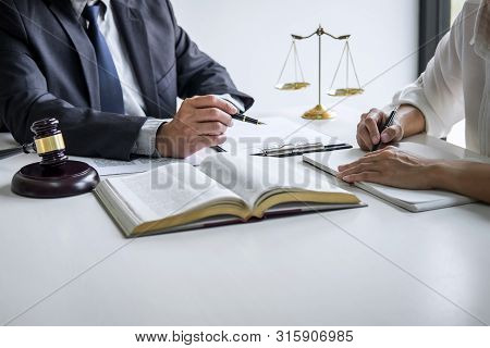 Consultation and conference of professional businesswoman and Male lawyers working and discussion having at law firm in office. Concepts of law, Judge gavel with scales of justice. stock photo