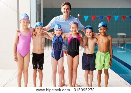 Portrait Of Male Coach With Children In Swimming Class Standing Edge Of Indoor Pool stock photo