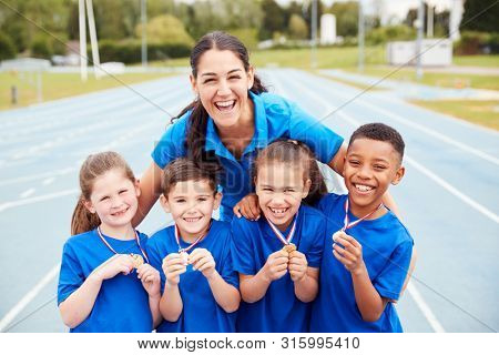 Portrait Of Children With Female Coach Showing Off Winners Medals On Sports Day stock photo