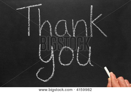 Writing the words thank you on a blackboard. stock photo