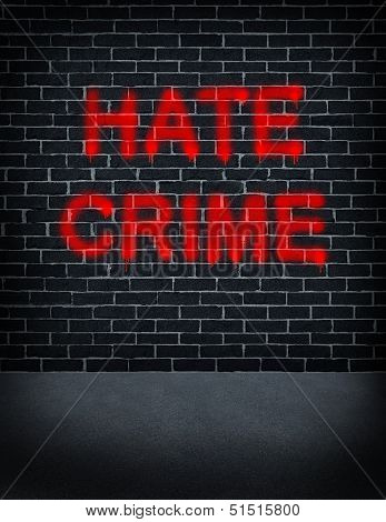 Hate crime social problem concept with a dark grey brick wall with spray can paint painted on the building structure as a symbol of racism and race discrimination as an illegal racial act of hatred and vandalism based on fear and xenophobia. stock photo