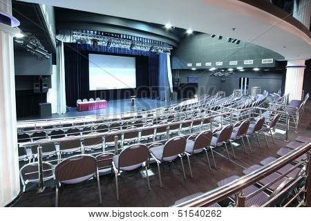 Document stand on stage and back of rows of chairs with handrails in big hall for business meetings.  stock photo