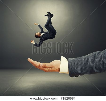 big palm catching small startled businessman in dark room stock photo