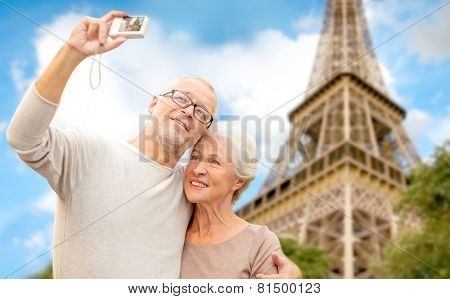 age, tourism, travel, technology and people concept - senior couple with camera taking selfie on str