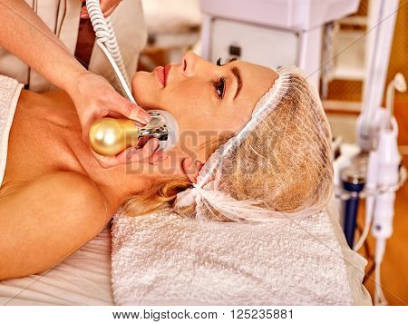 Close up of relaxed young woman receiving electroporation  facial therapy at beauty salon.  stock photo