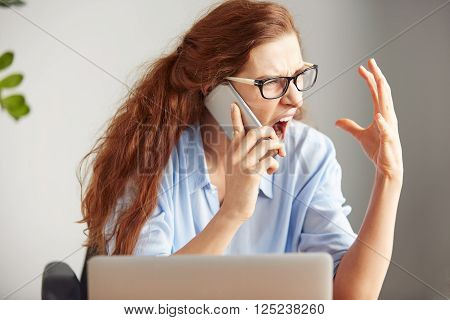 Headshot Of A Young Female Boss Shouting With Anger On The Cell Phone While Sitting At The Desk In H