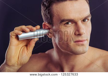 Portrait of handsome naked man using a hair trimmer for ears on a dark background stock photo