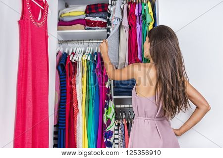 Home woman choosing her fashion outfit in dressing room. Woman in bedroom walk-in organized closet looking at clothes hanging deciding what shirt to wear in the morning. Shopping store clothing rack. stock photo