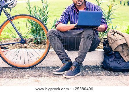 Indian man with laptop and sport bike sitting in city park - University asian student with pc and bicycle outdoor - Freelance young guy work with computer outside - Concept of modern green lifestyle