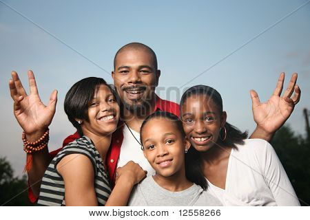 Happy African American family. Father with three teenage daughters together having a good time. stock photo