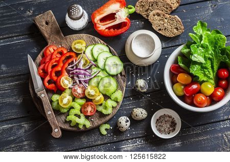 Fresh vegetables - tomatoes cucumbers peppers celery and garden herbs and spices on dark wooden background. Ingredients for fresh vegetable salad