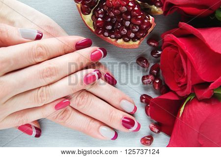 Skin care of a beauty female hands with grey pink and red asymmetry nail art manicure. And pockmarked grey background with red roses and sliced pomegranate stock photo