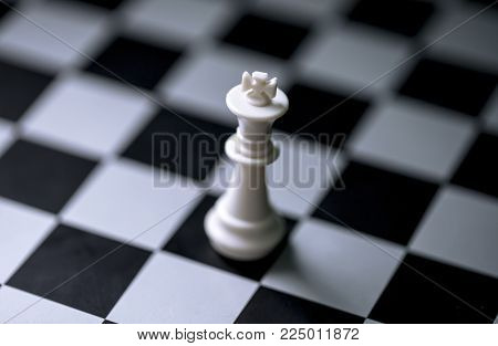 White king on chess board. Chess game figure on checkered board. White king alone on chessboard. Mate situation in chess rules. Business advantage or strong leadership concept. Chess king closeup stock photo
