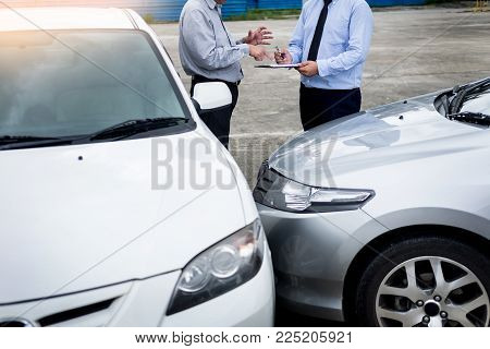 Insurance agent writing on clipboard while examining car after accident claim being assessed and processed stock photo