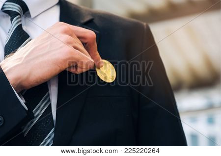 close up hand of smart business man in black suit pick coin from suit pocket on modern city background, digital technology, virtual currency, financial, investment, payment, saving money concept stock photo