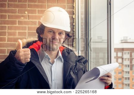 A construction worker gives you the thumbs up sign, signaling that everything is going well or the instruction was understood. Soft focus, toned stock photo