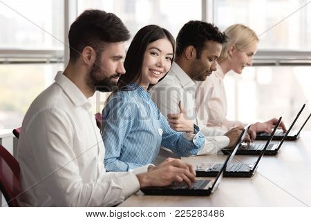 Japaneese girl accompanied with co-workers and shows thumb up. Female programmer accompanied with her team showing approval gesture, thumb up. stock photo