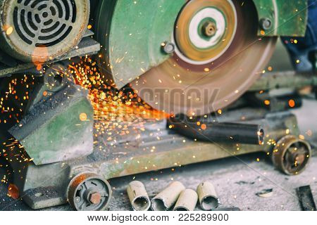 Metal cutting saw slicing through a steel pipe. stock photo