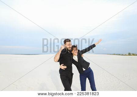 models man and woman come to seaside for photoshoot, young people jumping for joy among sands. Bearded guy wearing black shirt trousers and fair-haired lady in suit have good mood embrace. Concept of photosession, fashionable clothes or stylish outfits. stock photo