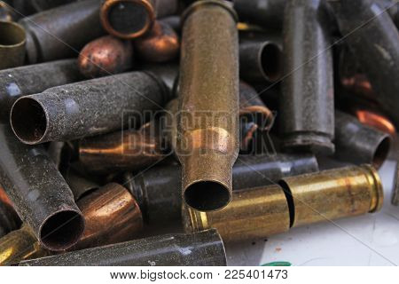 Heap of gun bullets. Weapon Cartridge case sleeve background texture, 7.65, and 9mm. Weapon cartridge sleeves.Gun bullet pattern close up.. stock photo