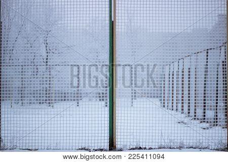 Snowed sport yard behind frosty metal grid net in winter time stock photo