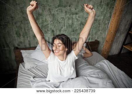 Young Smiling Woman Waking Up Happy After Healthy Sleep Stretching On Comfortable Bed With Sleeping