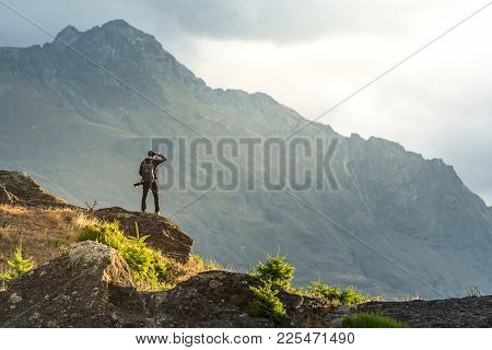 Young male photographer looking at mountain scenery during golden hour sunset in Queenstown, South Island, New Zealand. Travel and photography concept stock photo