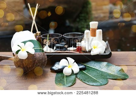 Spa massage compress balls, herbal ball on the wooden with treaments spa , Thailand, select focus stock photo