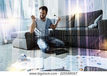 So angry. Young angry irritated man shouting and scrunching documents while sitting on the floor with diagrams in front of him and feeling furious stock photo