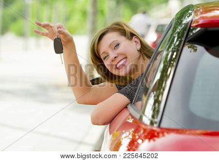 young happy attractive woman smiling proud sitting at driver seat holding and showing car key in new automobile buy and rent concept for insurance and rental advertising stock photo