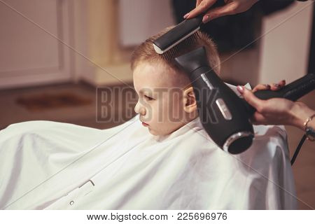Little boy at the hairdresser. Child is scared of haircuts. Hairdresser's hands making hairstyle to little boy, close up. Fashionable haircut for boys. stock photo
