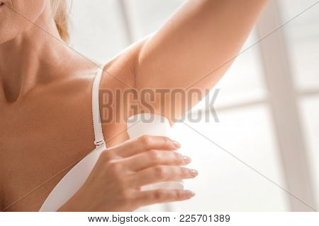 Fresh deodorant. Close up of a fresh deodorant being applied on an female armpit stock photo