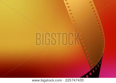 Camera negative film. Selective focus on film perforation. Unprocessed color motion picture film. Industry symbol for shooting process, photochemical laboratory process and film archive technology. Color gradient background. stock photo