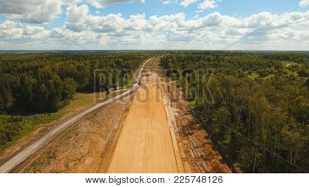 Construction of a new road in the forest area. Aerial view construction road place. Construction machinery for the construction of a road in the forest. stock photo