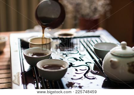 Man Pouring Puer Tea from Gaiwan Teapot at Traditional Chinese Tea Ceremony. Set of Equipment for Drinking Tea. stock photo