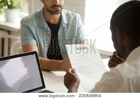 African american hr manager holding applicants curriculum vitae at job interview, black recruiter or employer considering cv of caucasian vacancy candidate during hiring negotiations, focus on resume stock photo