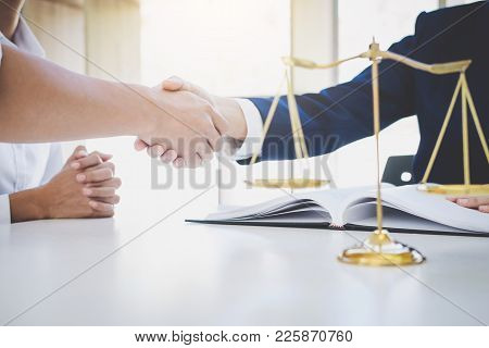 Handshake after good cooperation greeting, Having meeting with team at law firm, Consultation between a female lawyer and businessman customer, tax and the company of real estate concept. stock photo